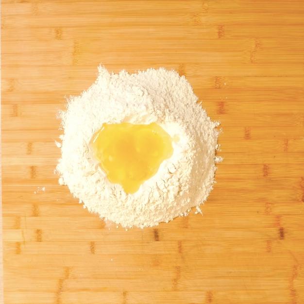 3. Realizzare poi una fontana di farina e metterci al suo interno: uova, sale e un cucchiaino di olio EVO