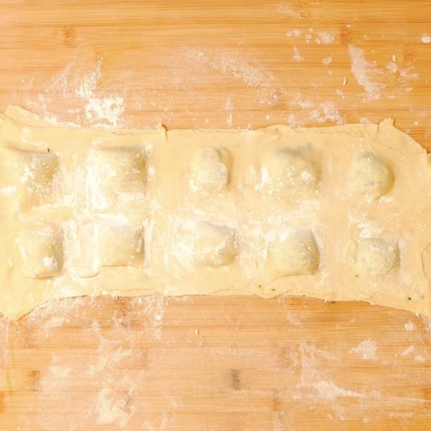 6. Disporre il ripieno sulla pasta divisa in quadrati, spennellare la pasta con acqua e sigillare con uno strato di pasta